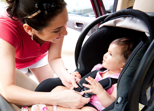 Happy smiling mother placing baby in car seat and closing belt for safety.